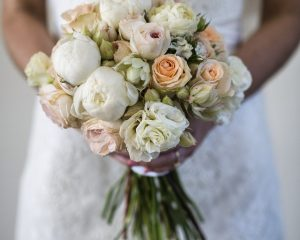 Hand held posy design of peonies, blushing brides, lisianthus and cottage roses