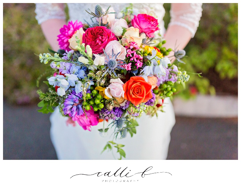 Bright wedding bouquet featuring roses, delphinium and sea holly