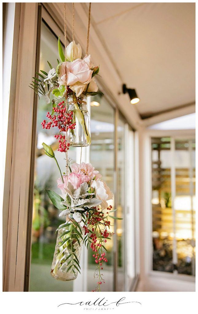 Reception hanging jars featuring roses and peppercorn berry