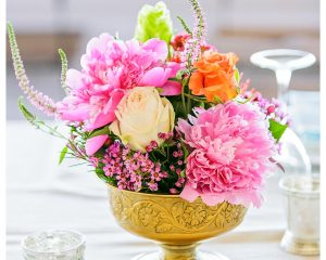 Gold vase with bright flowers including peonies