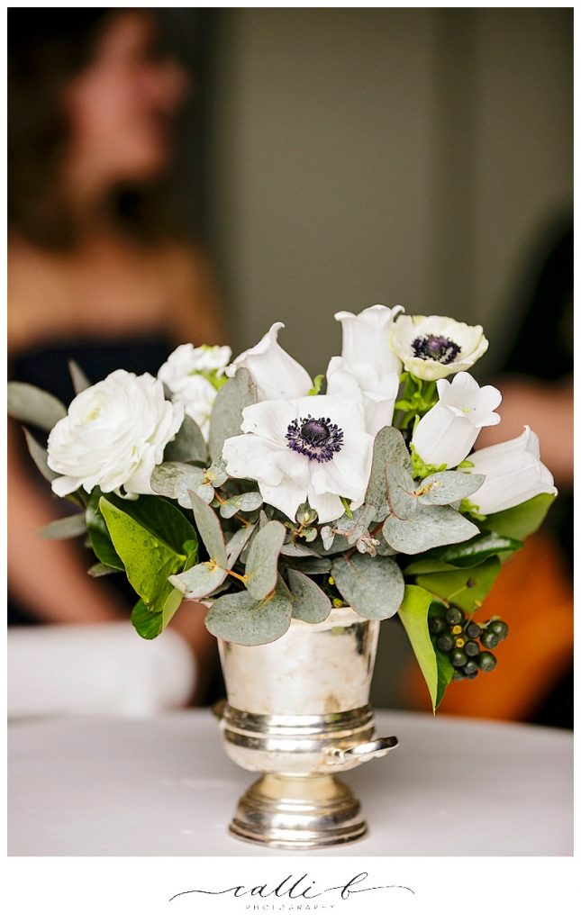 Silver vase featuring anemones and ranunculus