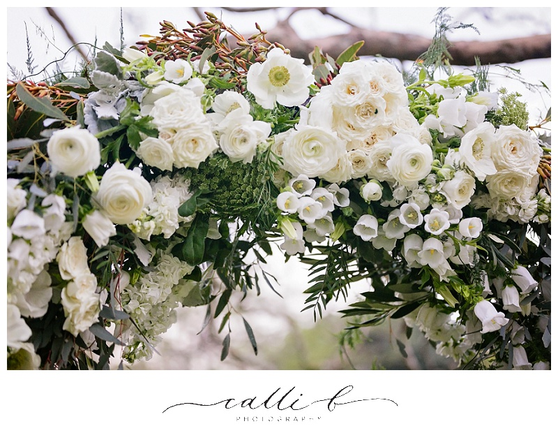 Ceremony arch flowers including roses and anemones