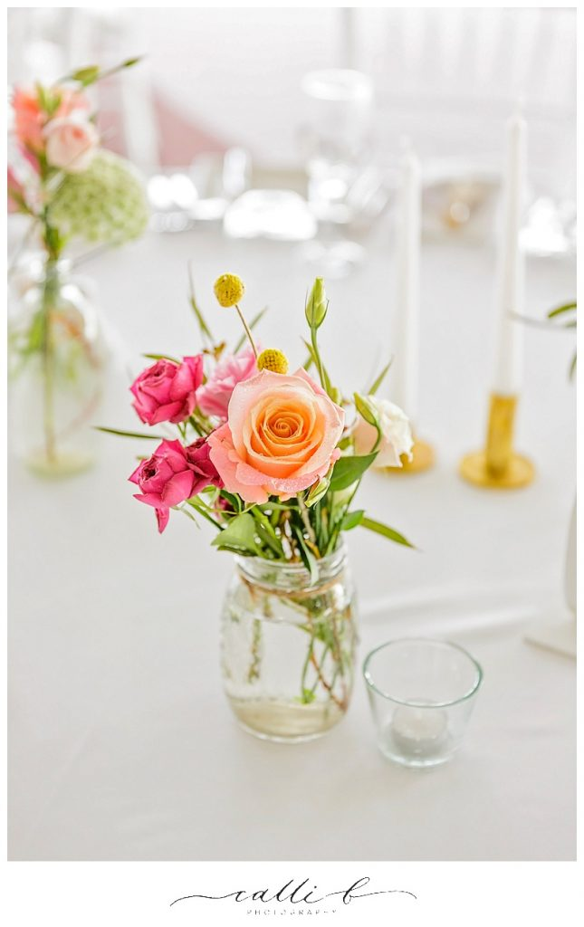 Mason jar with bright blooms including roses