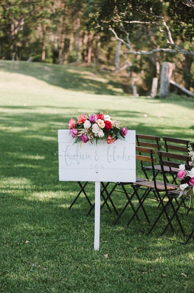 Bright ceremony entry sign flowers