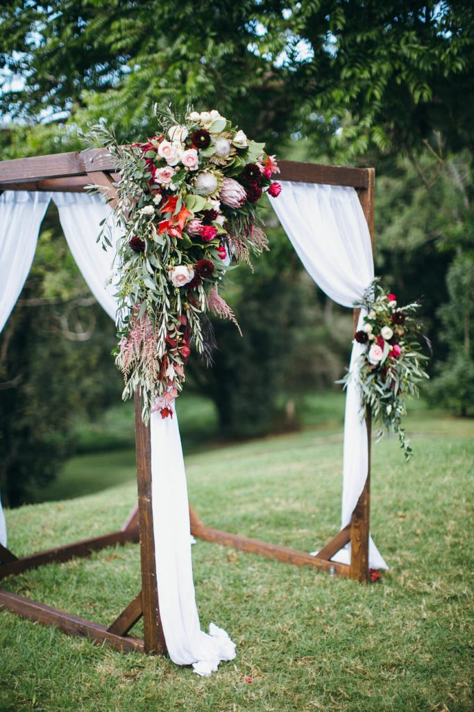 Rustic ceremony arbour featuring king proteas