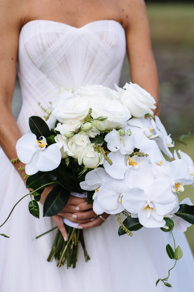 Modern white wedding bouquet featuring orchids