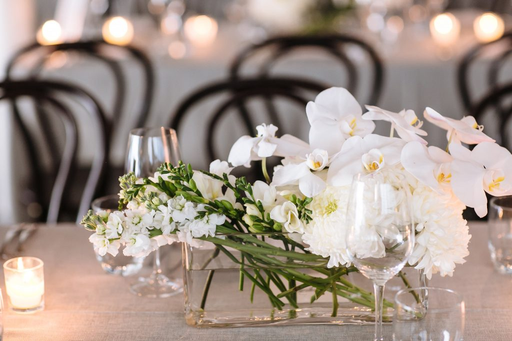 Modern white wedding flowers featuring orchids