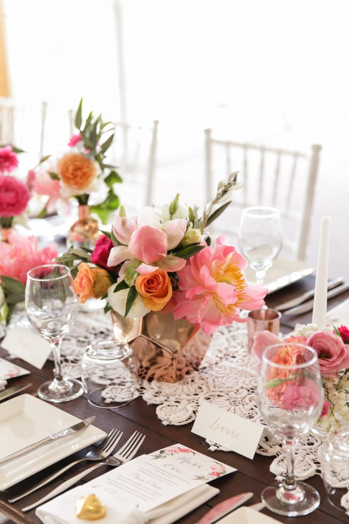 Copper vases and rose gold bottles featuring peonies