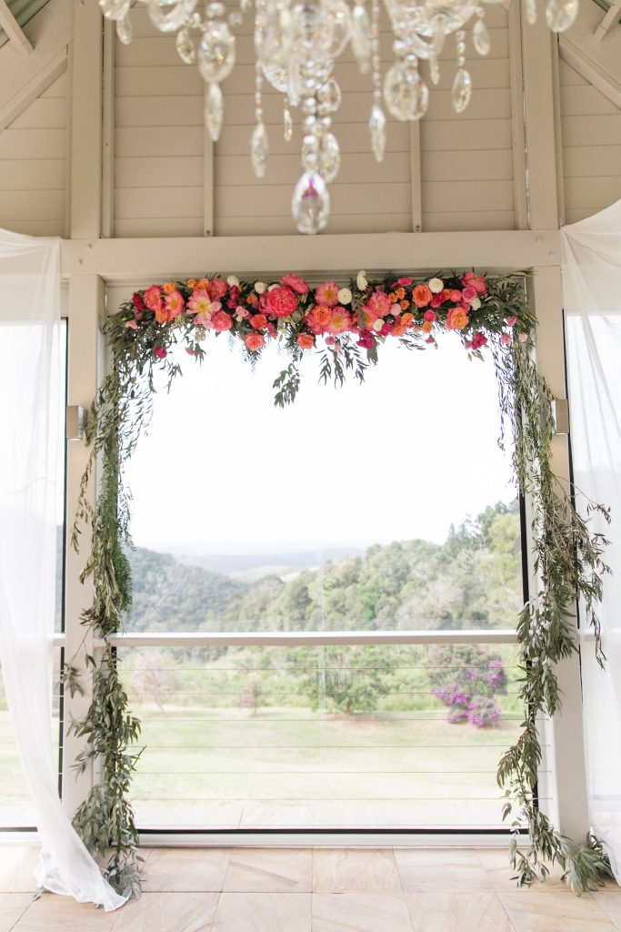 Ceremony hanging structure in croal and pink tones with whimsical greenery