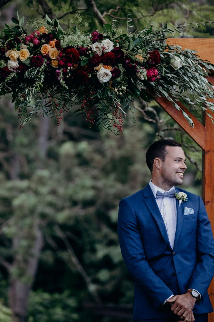 Ceremony arbour flowers in rich tones with rustic greenery
