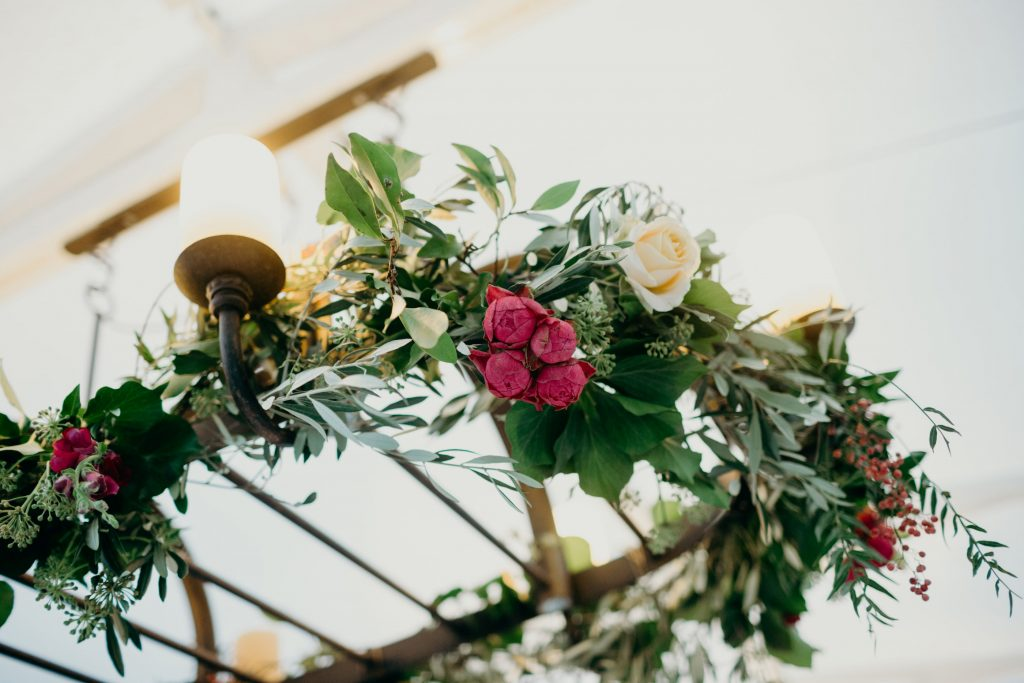 Chandeliers wrapped with rustic foliages and feature blooms