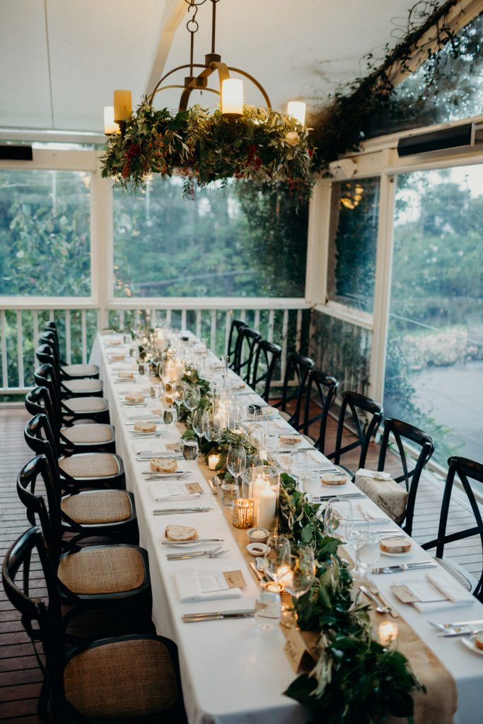Reception tables with lush greenery garlands