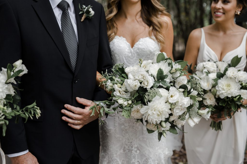 Modern white wedding bouquet featuring dahlias and lisianthus