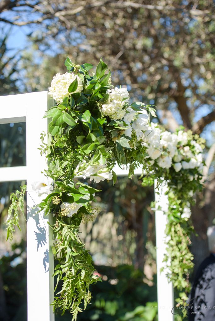 Lush white and green ceremony canopy featuring roses