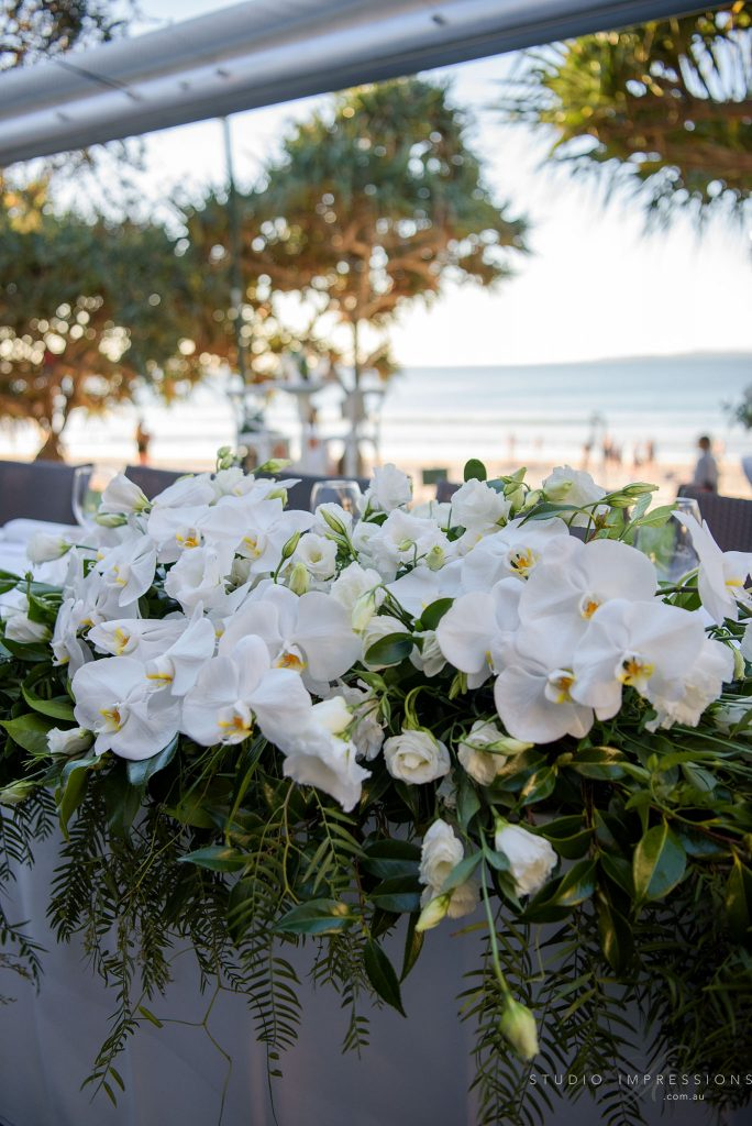 Bridal table garland featuring orchids and lush green