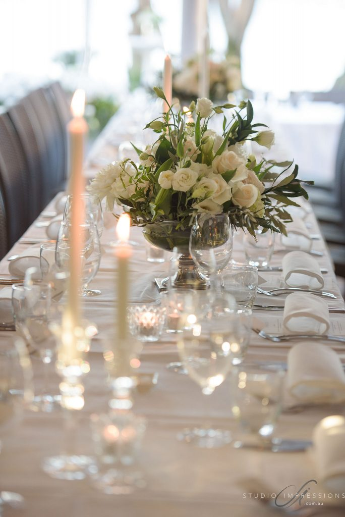 Silver footed chalice vase designs featuring white blooms and sage greenery