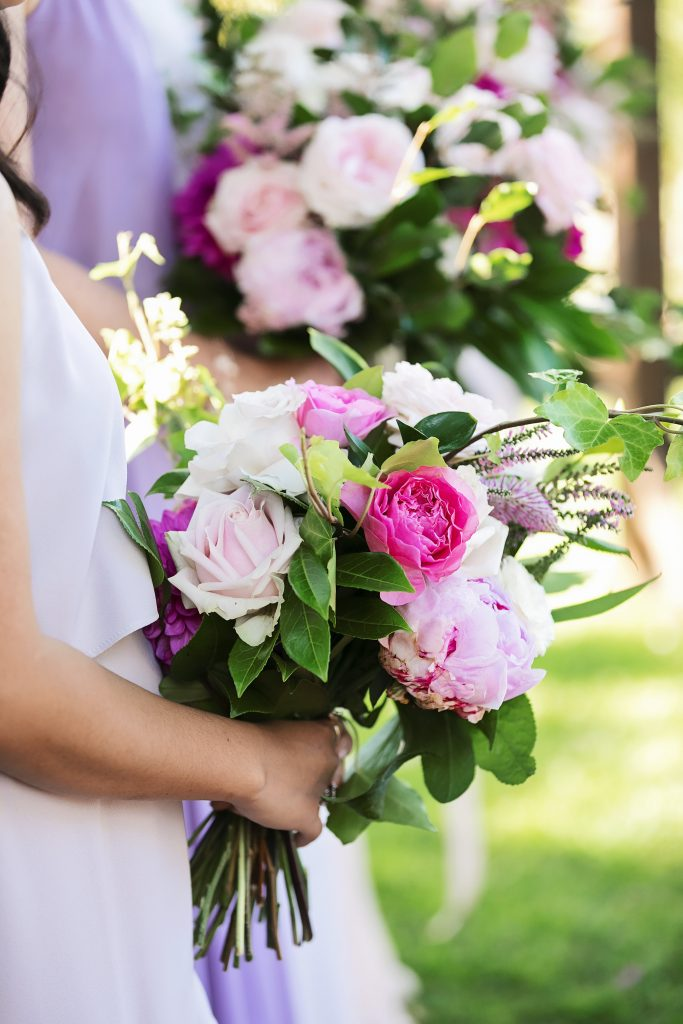 Crescent style wedding bouquet in pink tones featuring roses