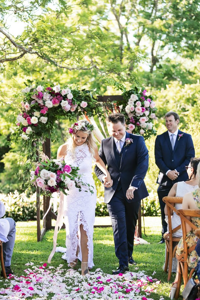 Pink floral wedding arbour and rose petal path