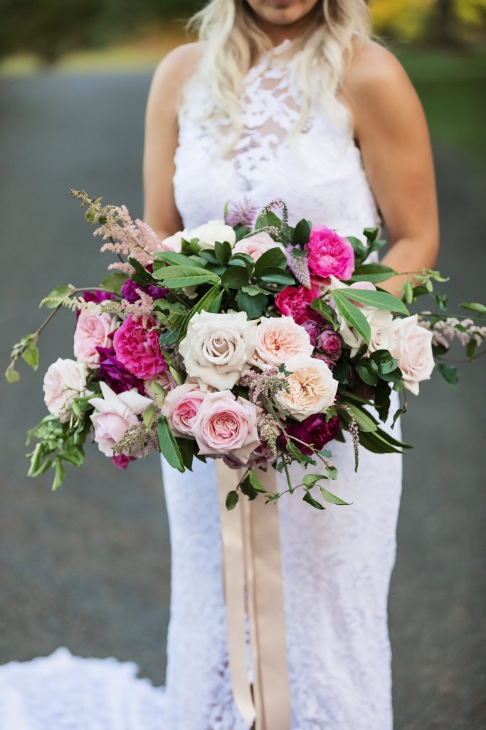 Pink wedding bouquet featuring roses and peonies
