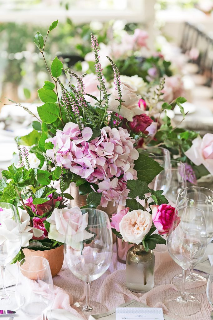 Eclectic copper vases and bottles with pink blooms