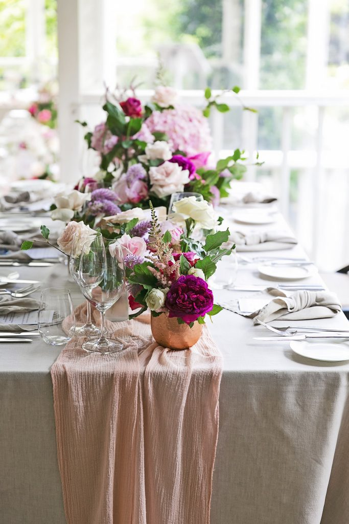 Eclectic rose gold bowls and two toned bottles with pink blooms