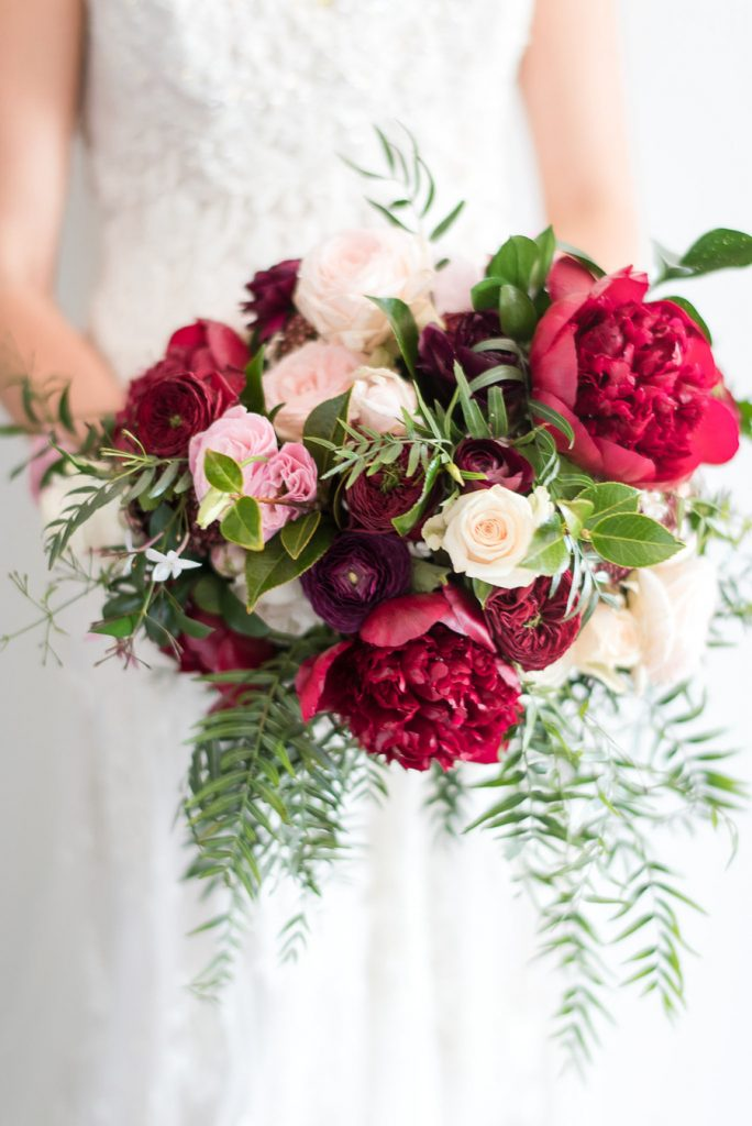 Rich toned wedding bouquet featuring peonies