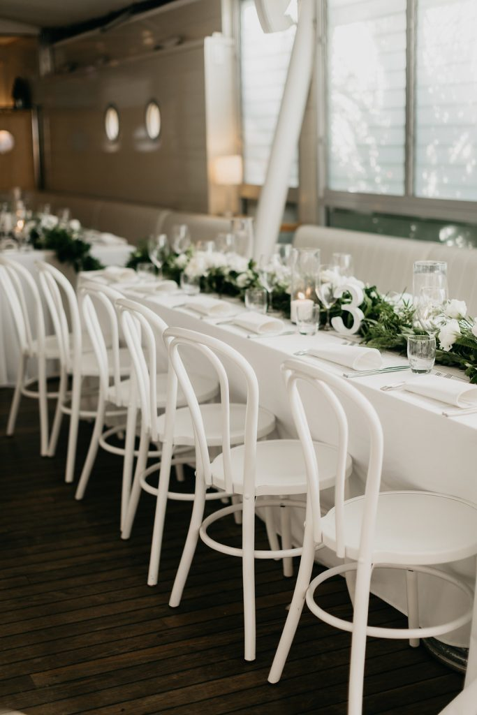 Table garlands with lush dark greenery and white feature blooms