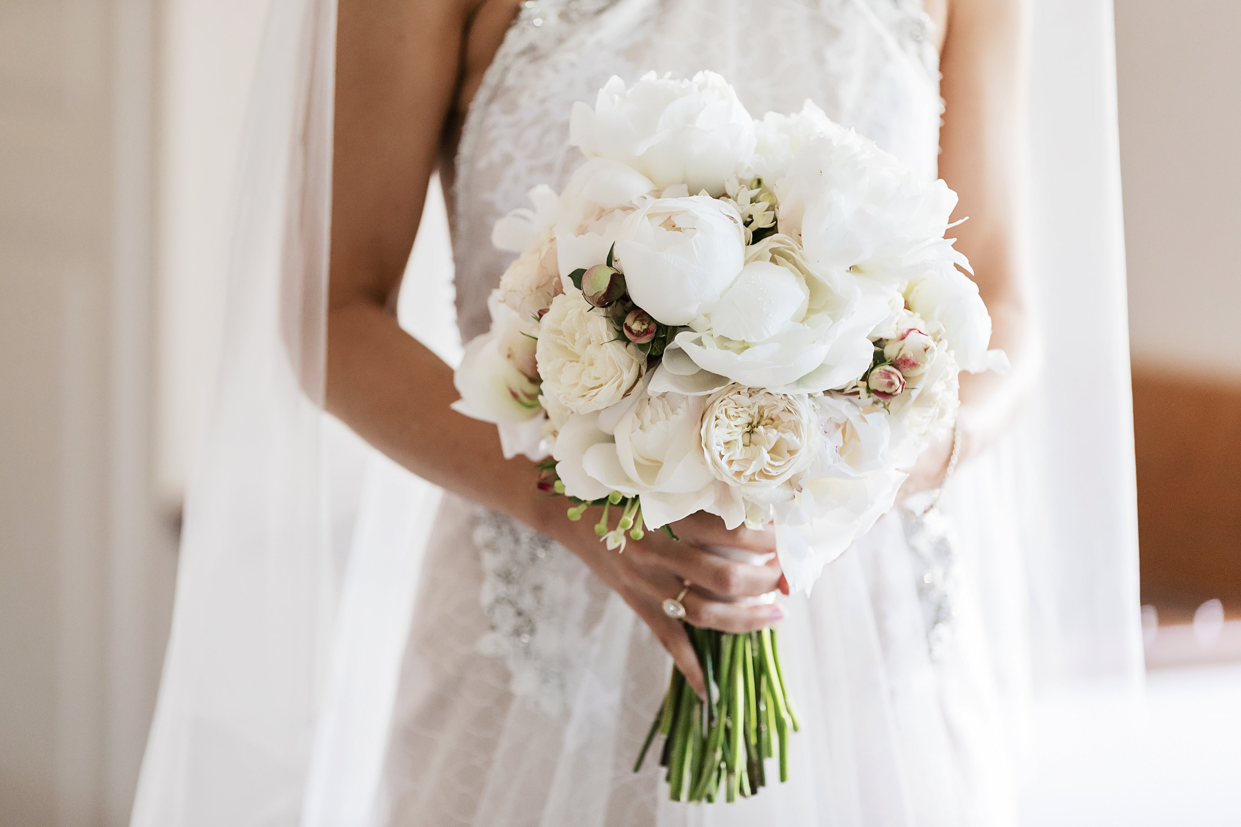 Modern white wedding bouquet featuring peonies