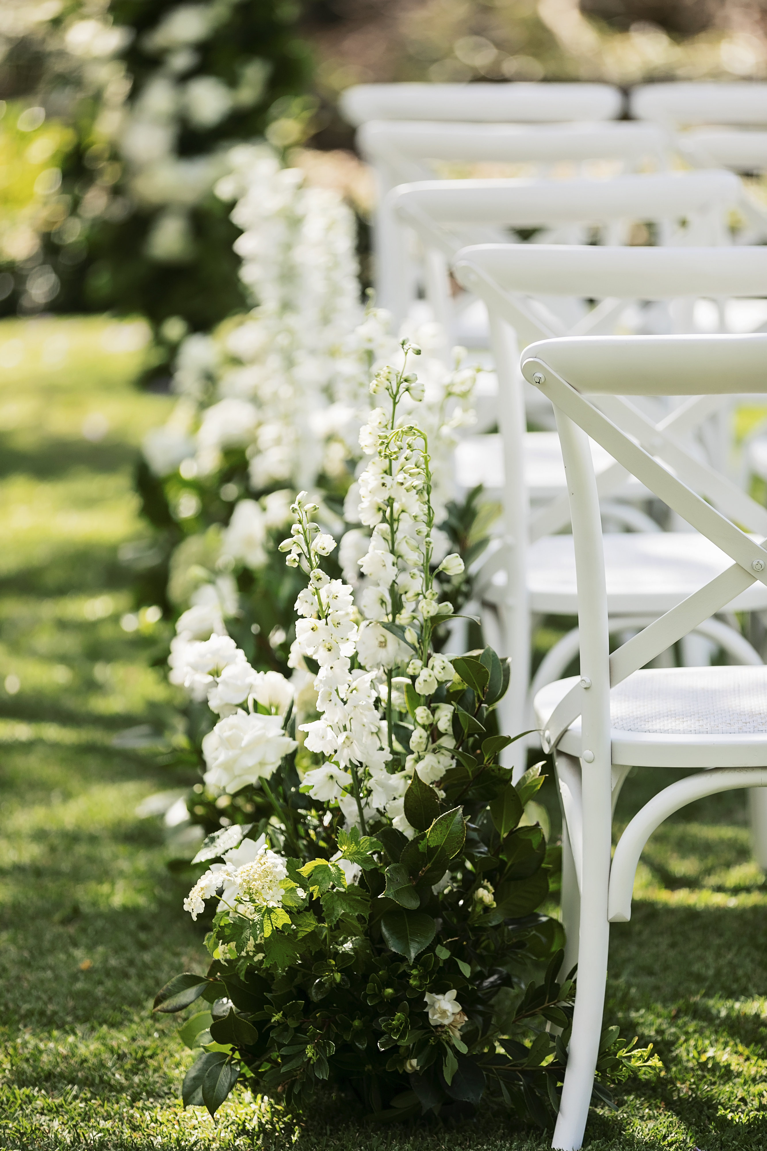 Ceremony aisle hedging of lush greenery and white blooms