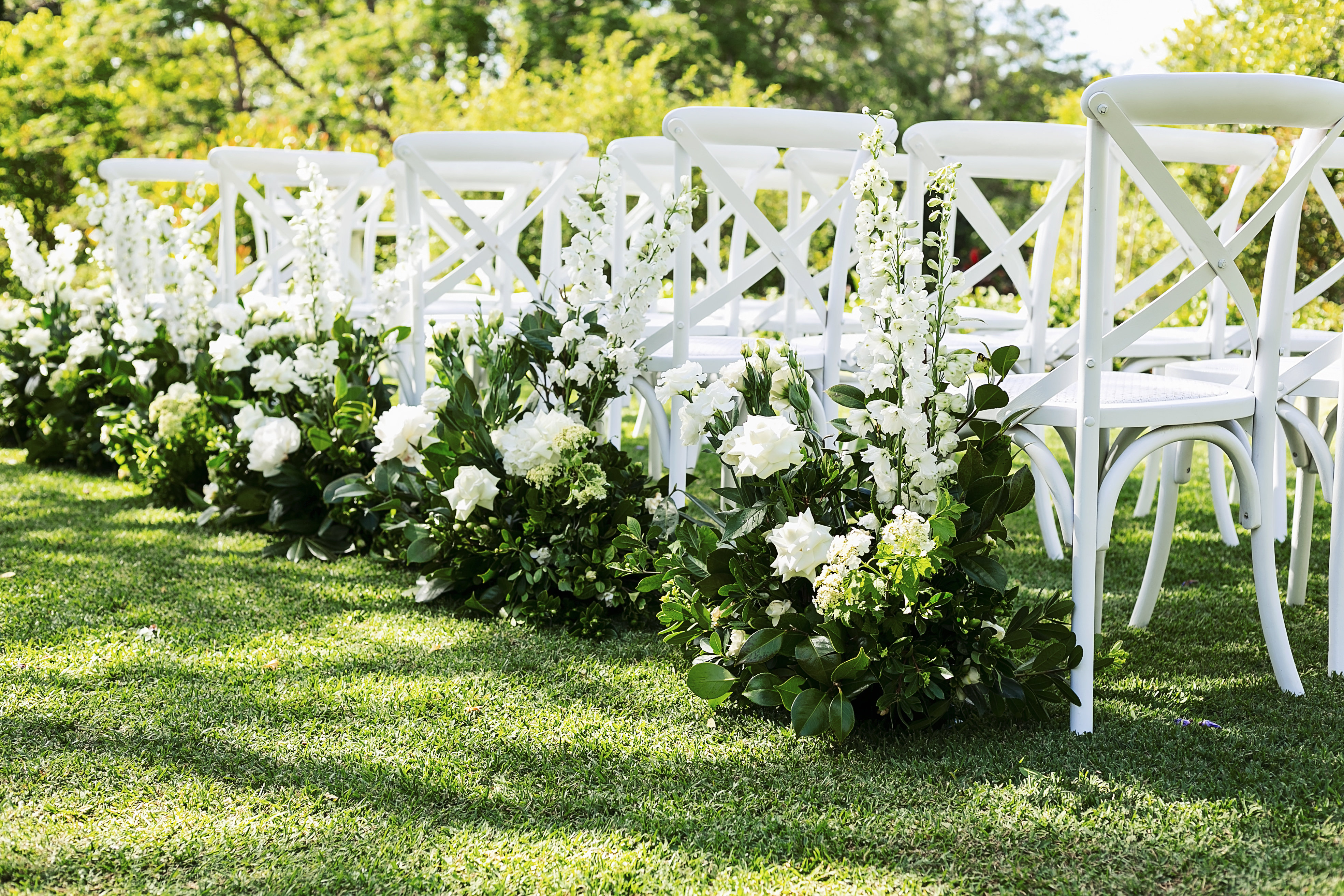 Ceremony aisle hedging with lush greenery and white delphinium