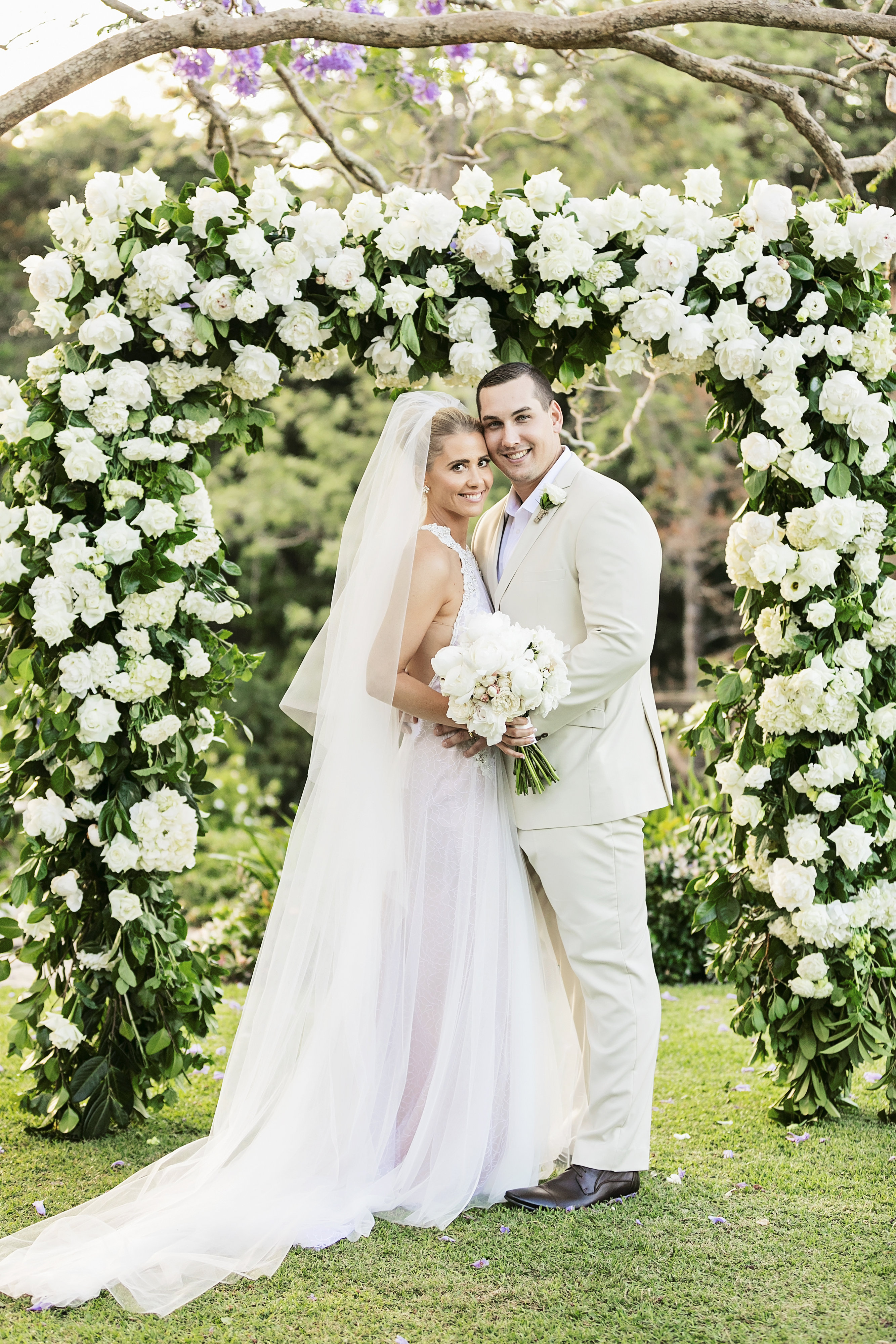 Ceremony arbour featuring lush greenery and white blooms