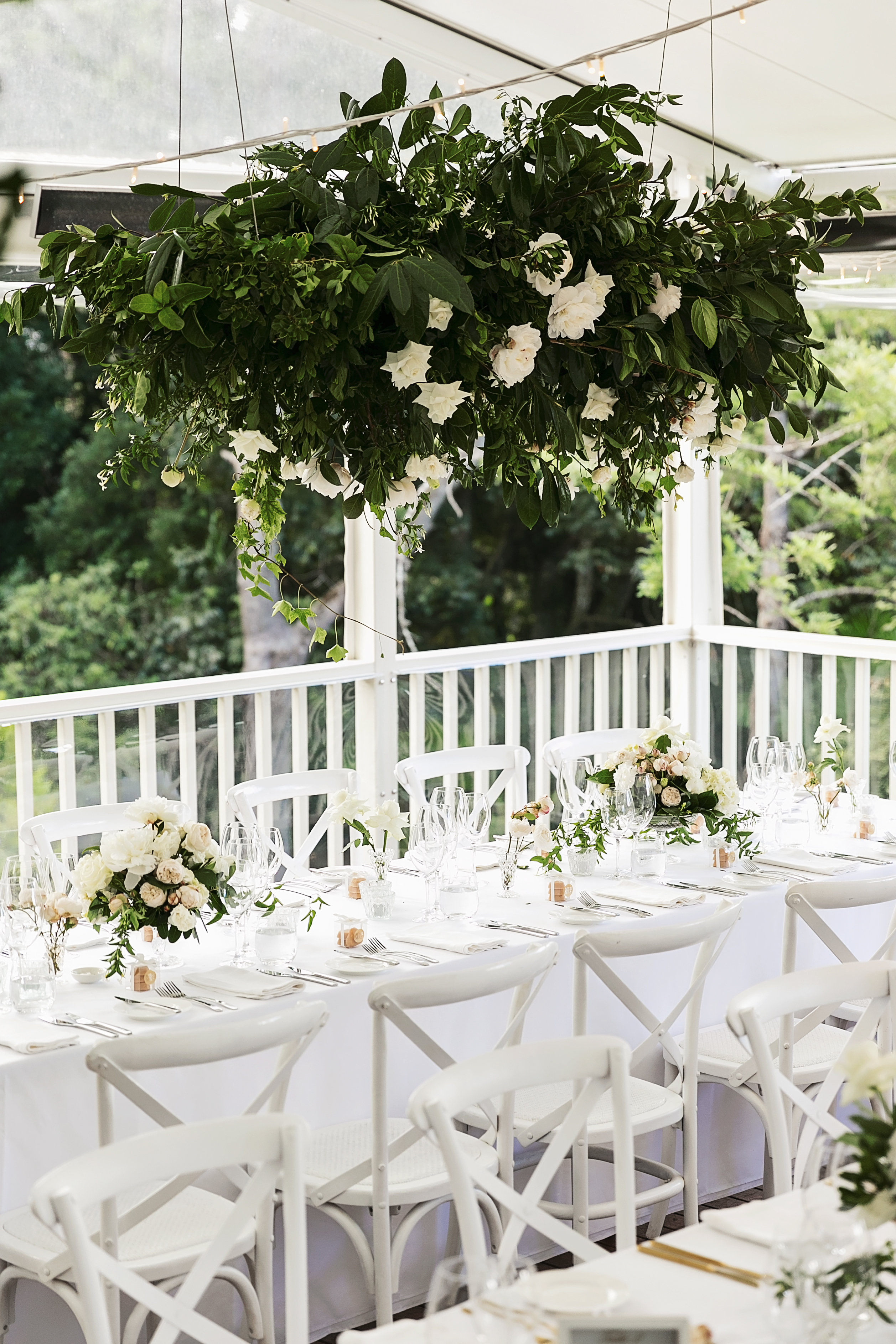 Hanging installation with lush greenery and white roses