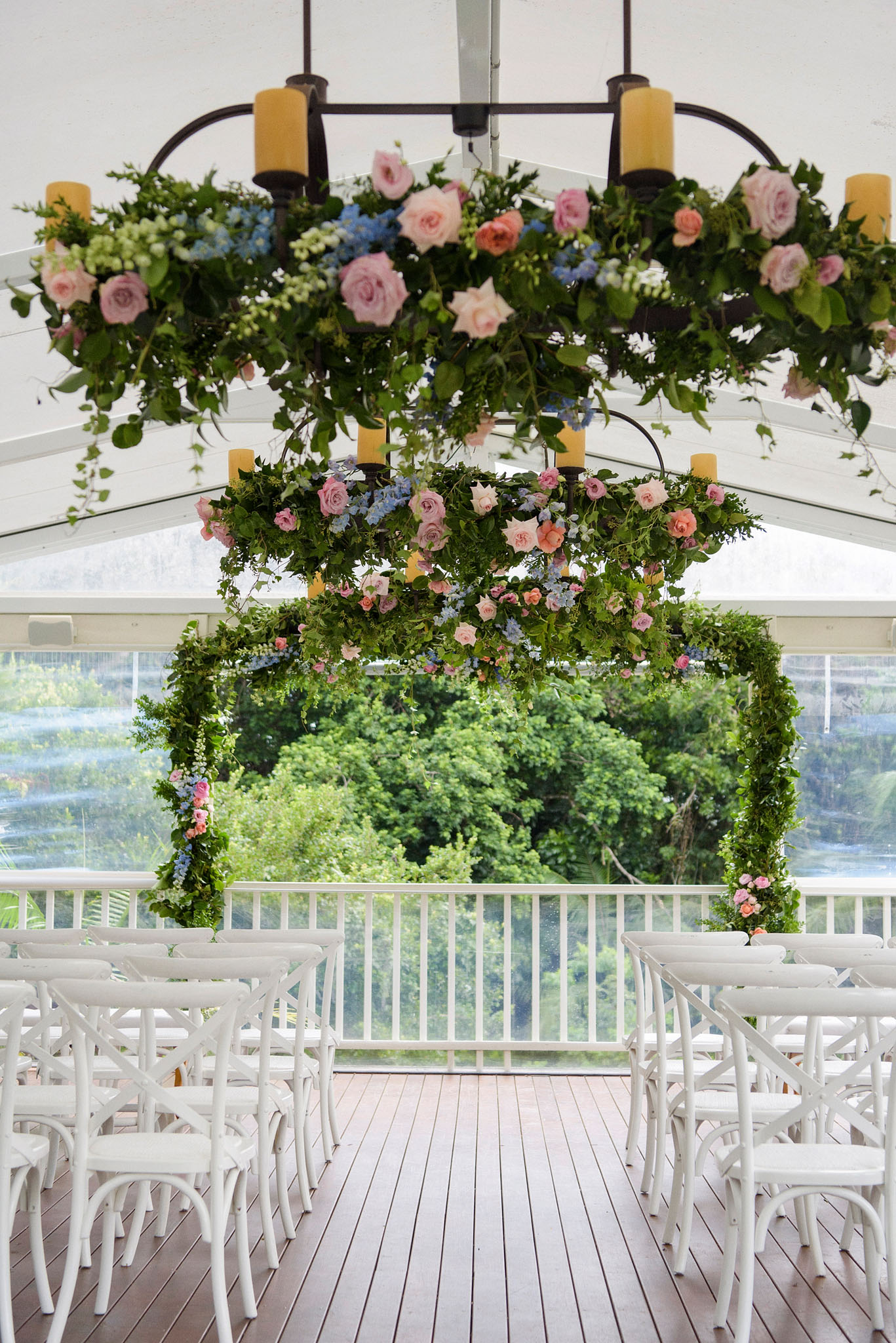 Chandelier wraps featuring lush greenery and pastel blooms