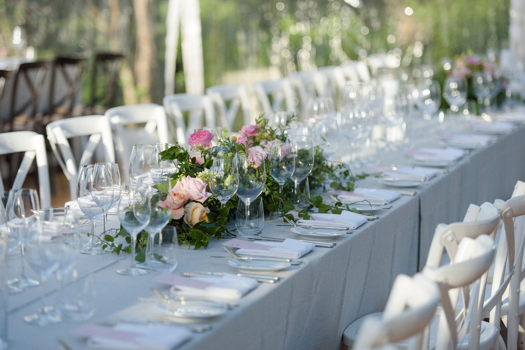 Low lying modern table arrangements with lush greenery and pastel blooms