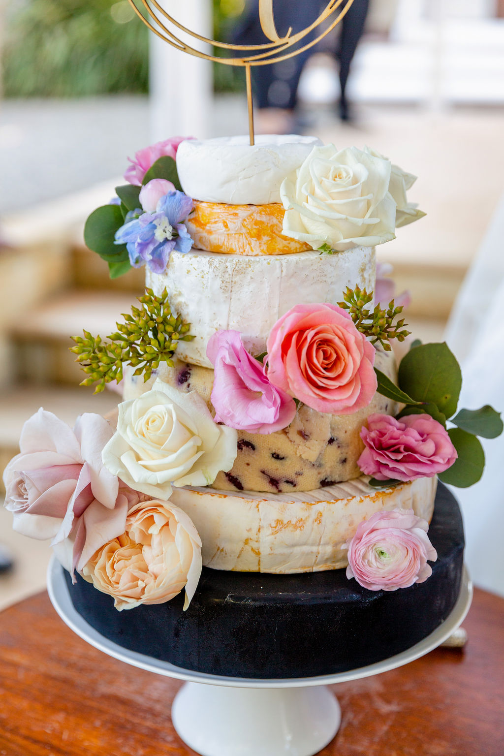 Cheese wheel wedding cake with pastel blooms