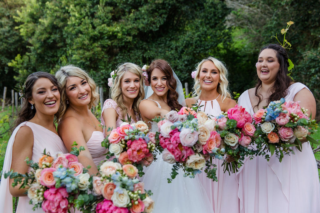 Pretty pastel wedding bouquets featuring peonies, roses and ranunculus