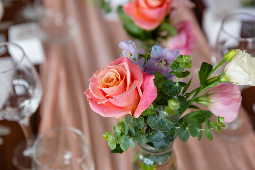 Reception bottles featuring coral roses and gum