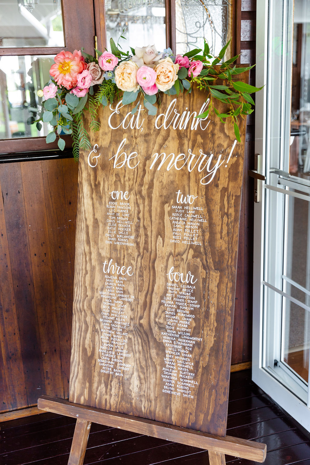 Seating board sign floral featuring coral peonies and pale pink ranunculus