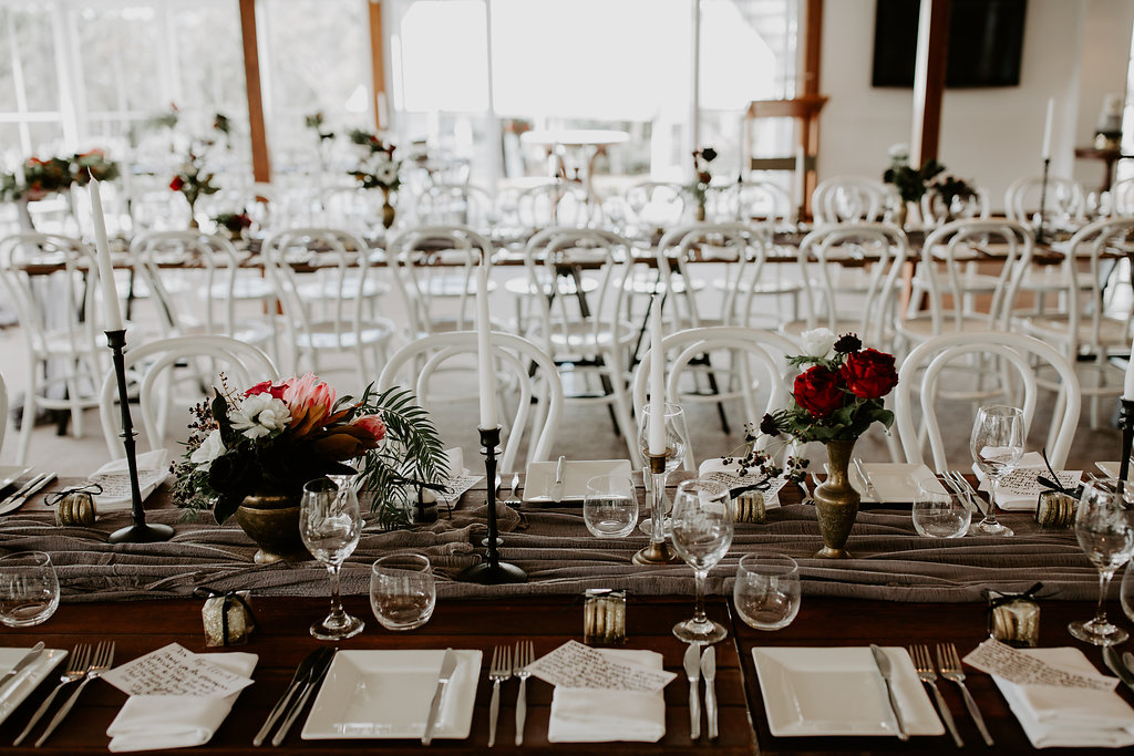 Reception brass vases featuring anemones and red roses