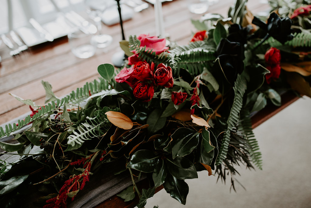 Table garland featuring lush greenery and rich toned blooms