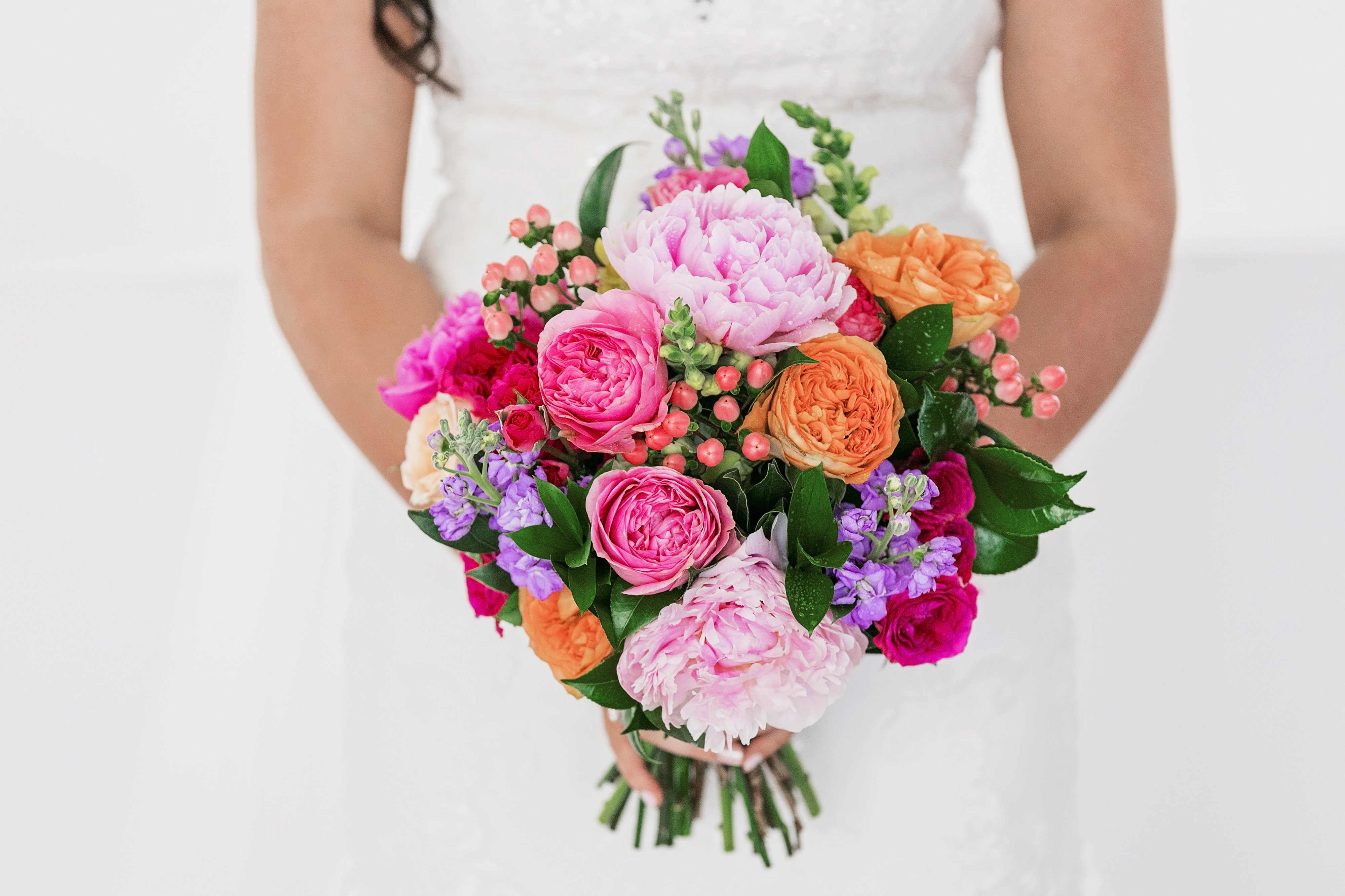 Bright wedding flower bouquet featuring pink peonies