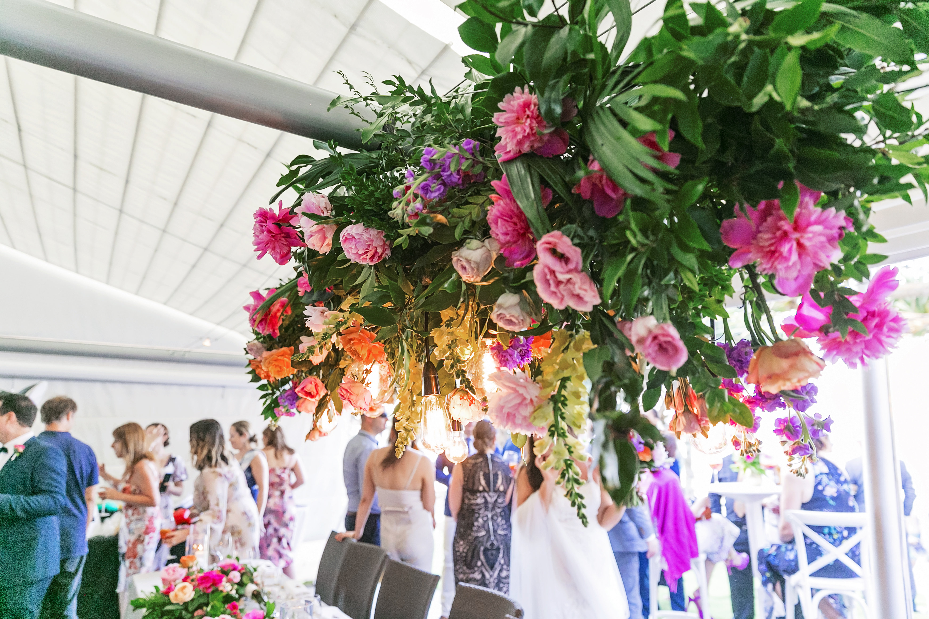 Noosa wedding featuring mordern bright floral hanging structure