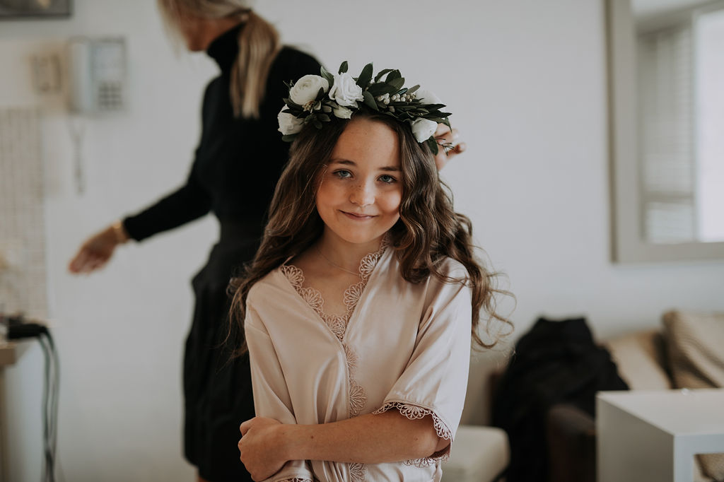 Flower girl halo in white tones with lush greenery