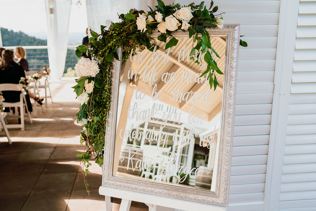 Entry sign floral featuring lush greenery and white blooms