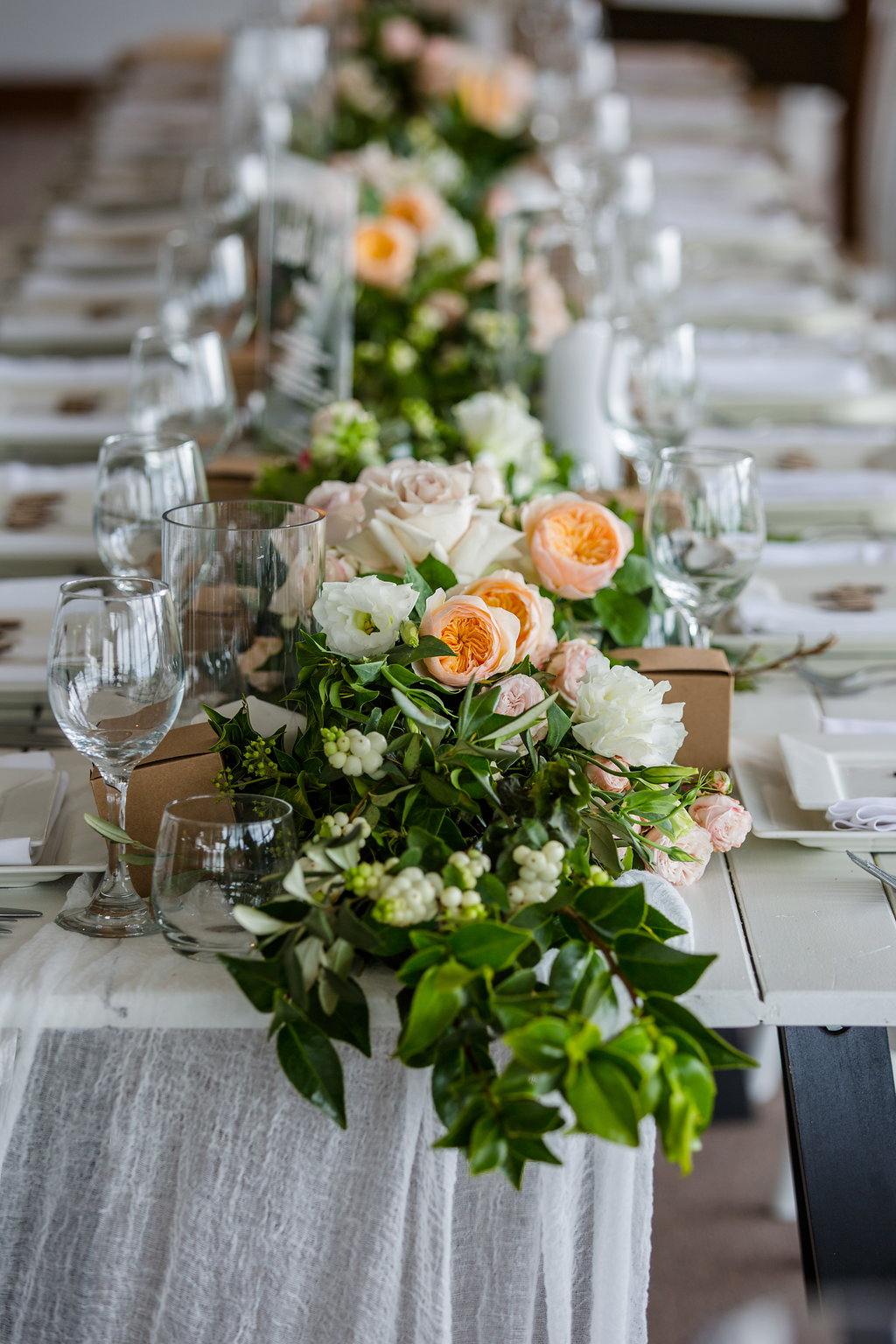 Reception table garlands with lush greenery and pastel blooms