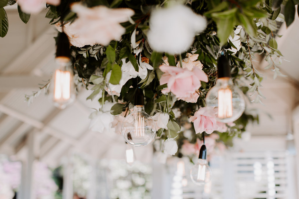 Hanging installation featuring roses and lush greenery