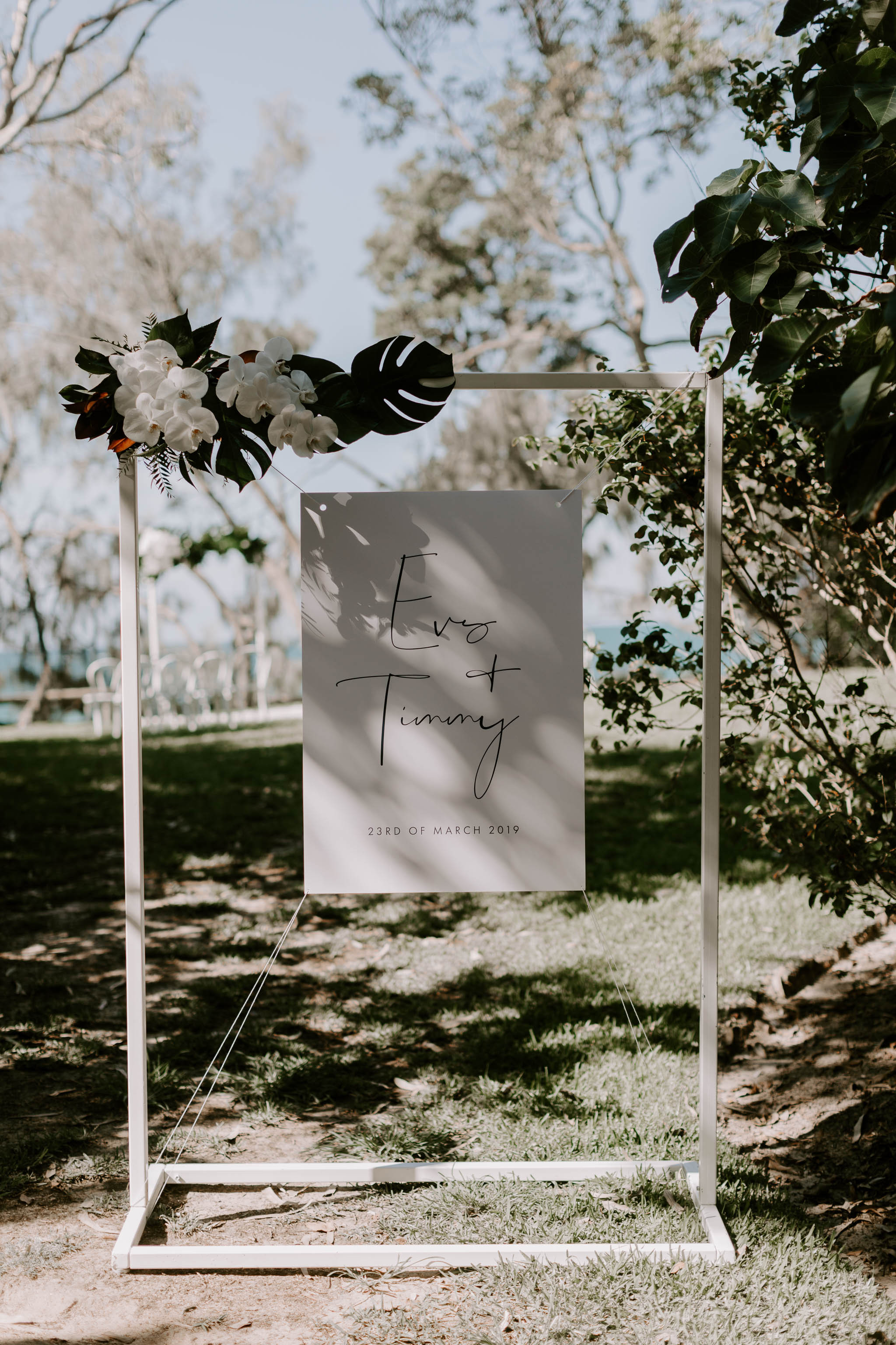Ceremony entry sign featuring orchids and tropical leaves