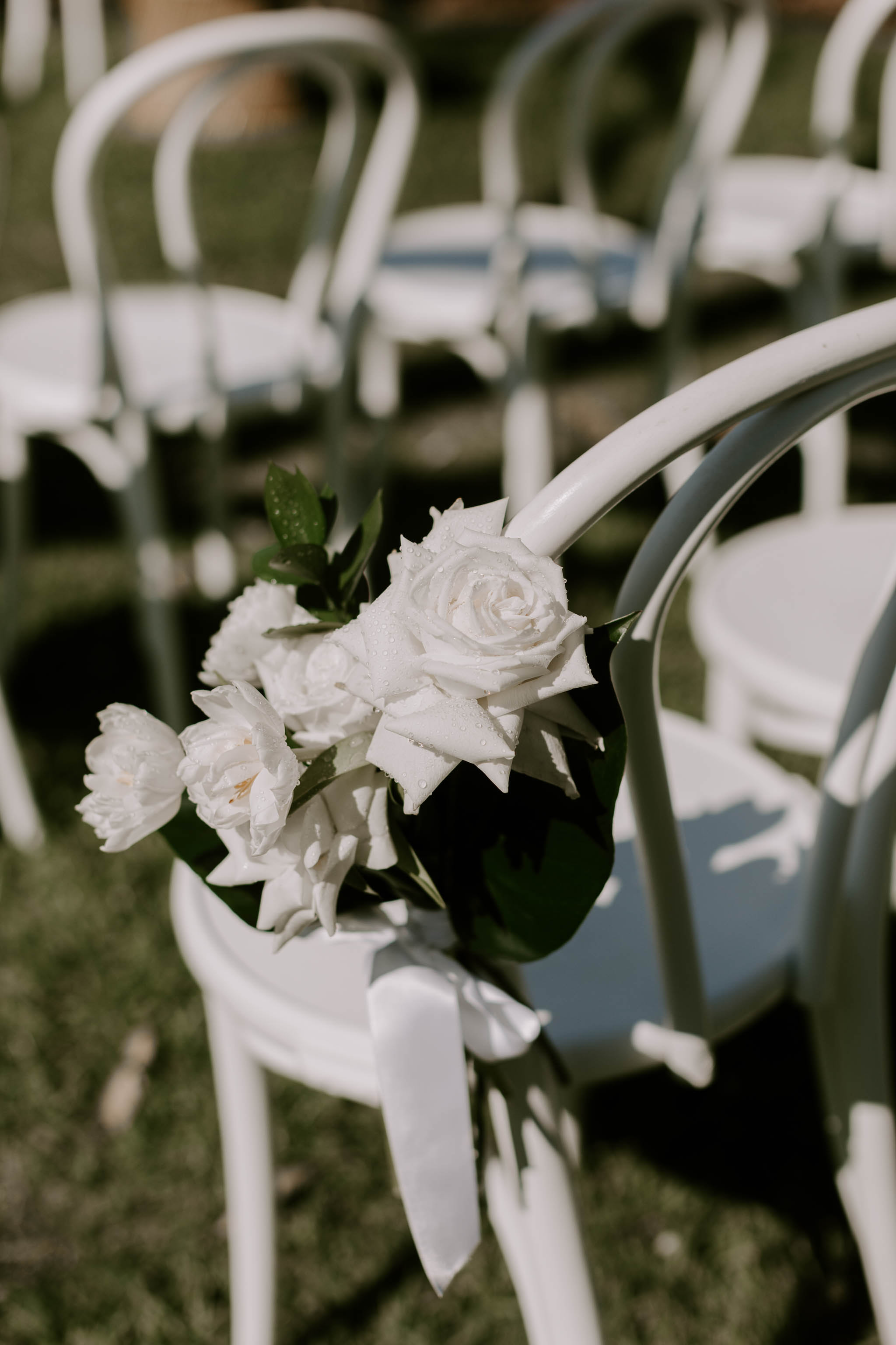 Chair posies with white blooms and tropical leaves