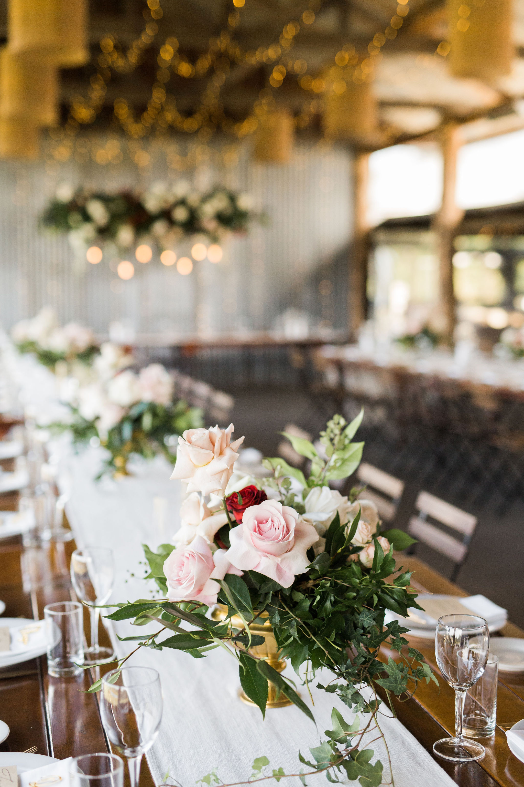 Soft pink roses, with pops of burgundy and lush greenery