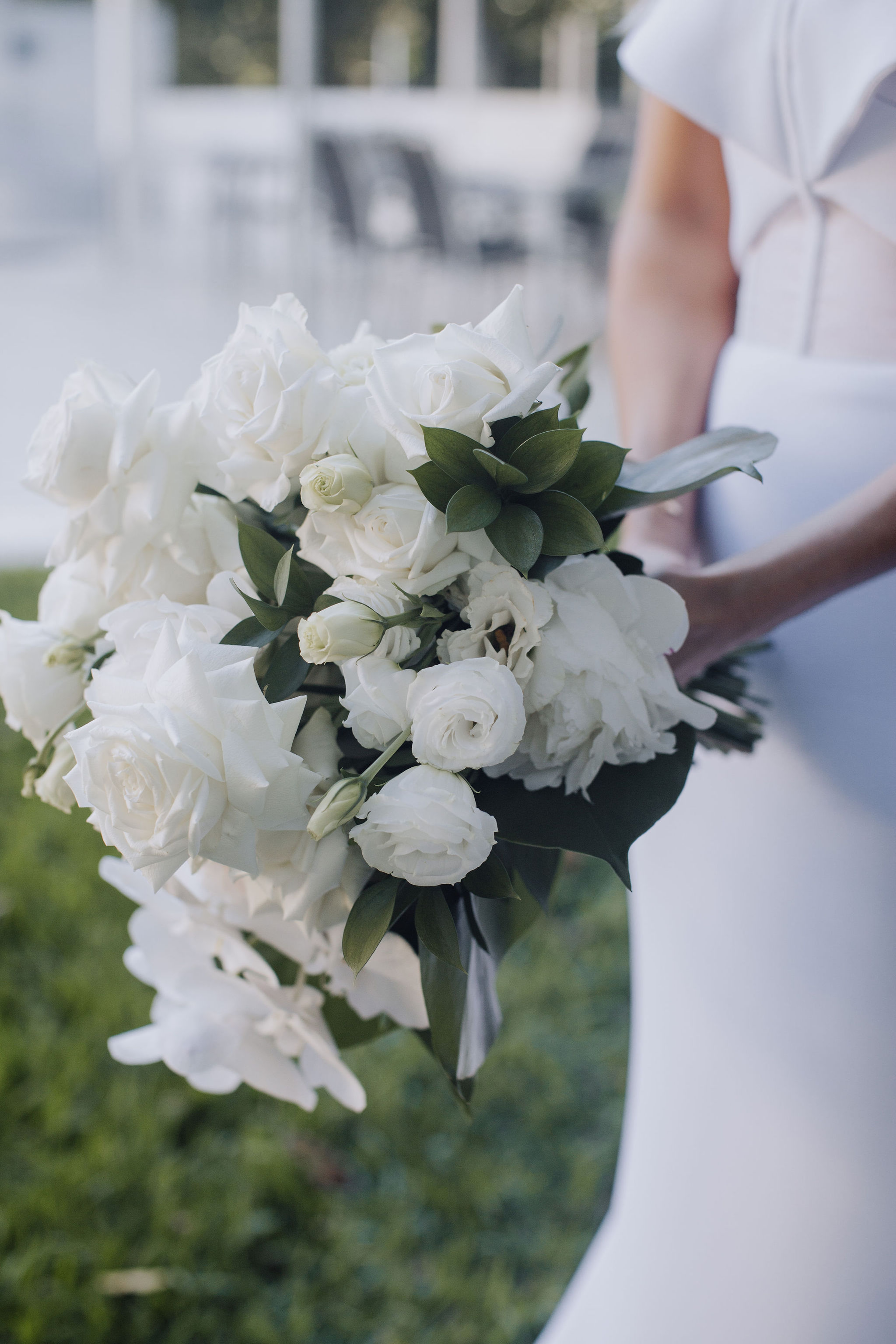 White wedding bouquet featuring orchids and tropical leaves